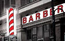 A barber pole in front of a barbershop